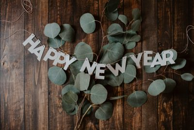 Eucalyptus leaves on a wooden background with the letters spelling Happy New Year strung together on top.