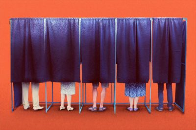 People standing in voting booths with the curtains closed.