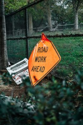 Road Work Ahead sign leaning on a chain link fence